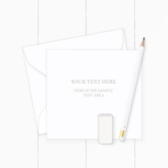 Płaski świecki widok z góry elegancka biała kompozycja papierowa koperta ołówek i gumka na podłoże drewniane.