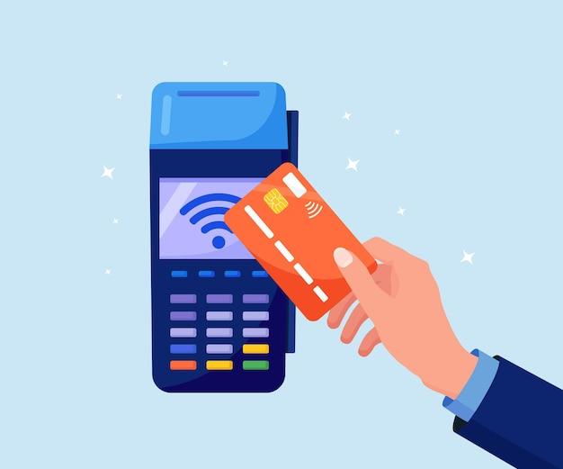 Płatność zbliżeniowa. ludzka ręka trzyma kartę kredytową lub debetową w pobliżu terminala pos do zapłaty. transakcja za pomocą technologii nfc