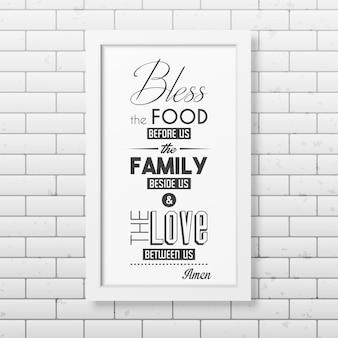 Pobłogosław jedzenie przed nami - cytuj typograficzną realistyczną białą kwadratową ramkę na ścianie z cegły.