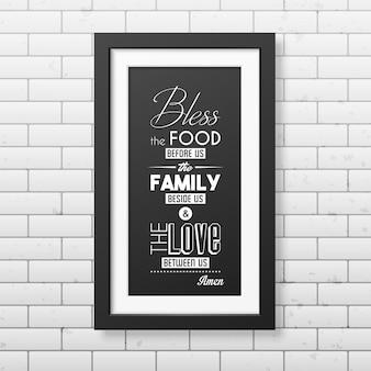 Pobłogosław jedzenie przed nami - cytuj typograficzną realistyczną kwadratową czarną ramkę na ścianie z cegły.