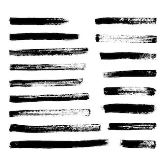 Pociągnięcia pędzlem czarny grunge. zestaw siedemnastu pasków pomalowanych tuszem. miejsce atramentu na białym tle. ilustracja wektorowa