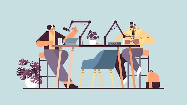 Podcasterzy rozmawiają z mikrofonami nagrywają podcast w studio podcasting koncepcja nadawania radia internetowego mężczyzna w słuchawkach wywiad kobieta pełna długość pozioma