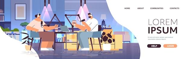 Podcasterzy rozmawiają z mikrofonami nagrywają podcast w studiu podcasting koncepcja nadawania radia internetowego mężczyzna w słuchawkach wywiad kobieta pełna długość kopia przestrzeń pozioma