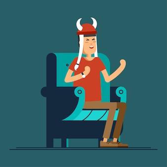 Podekscytowany chłopak, fan sportu, ogląda telewizję na wygodnym fotelu.