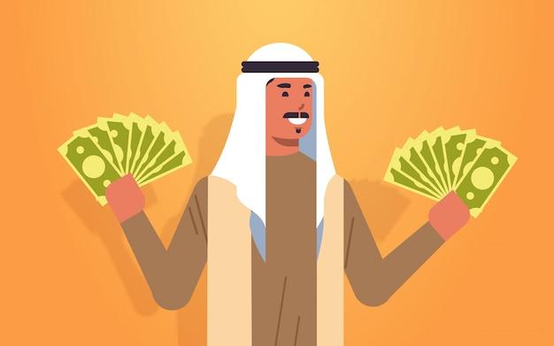 Podekscytowany mężczyzna arabski gospodarstwa weksle sukces finansowy sukces bogactwo koncepcja bogaty biznesmen z banknotów dolara poziome portret