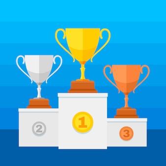Podium zwycięzców konkursu ze złotymi, srebrnymi i brązowymi pucharami trofeów