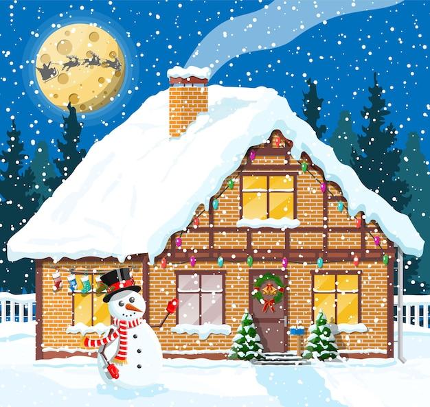 Podmiejski dom pokryty śniegiem. budynek w świątecznym ornamentie. choinka krajobrazowa, bałwan, renifery sanie świętego mikołaja. dekoracja noworoczna. wesołych świąt bożego narodzenia święto. ilustracja