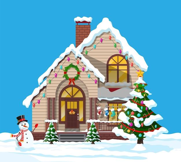 Podmiejski dom pokryty śniegiem. budynek w świątecznym ornamentie. świerk choinkowy, bałwan. dekoracja szczęśliwego nowego roku. wesołych świąt bożego narodzenia. nowy rok i święta bożego narodzenia. ilustracja