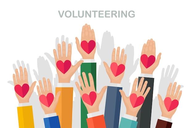 Podniesione ręce z kolorowym sercem. wolontariat, dobroczynność, koncepcja oddawania krwi.