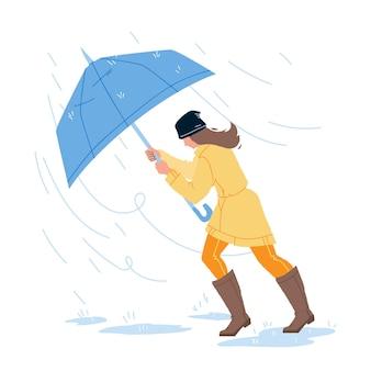 Pogoda deszcz dzień spaceru dziewczyna z parasolem wektor. młoda kobieta spacer w deszczowej i wietrznej pogody burzowej. postać pani nosząca płaszcz przeciwdeszczowy, spodnie i kalosze płaskie ilustracja kreskówka