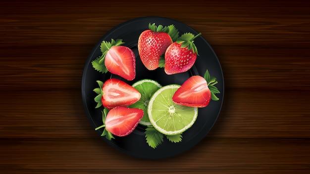 Pokrojony wapno i truskawki na ciemnym talerzu i drewnianym stole.