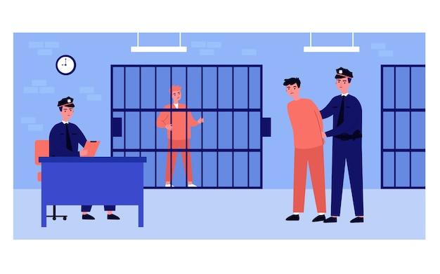Policjanci i aresztowani mężczyźni w komisariacie policji