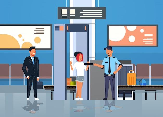 Policjant sprawdzający pasażerów i bagażu w wykrywacz metali brama rentgenowska skaner całego ciała skaner lotniska kontrola bezpieczeństwa wydział terminal wnętrze