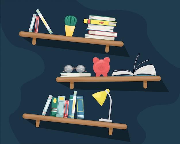 Półki ścienne z książkami, kaktusem, skarbonką, lampką stołową i szklankami.