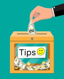 Pomarańczowe pudełko na napiwki pełne gotówki. dzięki za usługę. pieniądze na serwis. dobre opinie lub darowizny. koncepcja napiwku.
