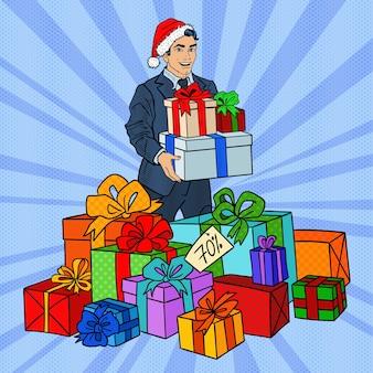 Pop art man w santa hat z prezentami na świąteczną wyprzedaż.