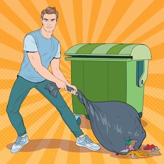 Pop art młody człowiek trzyma worek na śmieci. facet ze śmierdzącym workiem na śmieci.