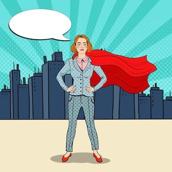 Pop art pewna kobieta biznesu superbohatera w garniturze z czerwoną peleryną.
