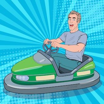 Pop art podekscytowany mężczyzna jadący samochodem bumber na wesołym miasteczku. facet w samochodzie elektrycznym w parku rozrywki.