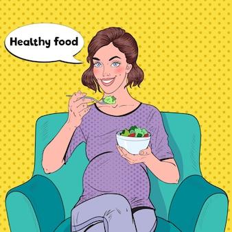 Pop art szczęśliwa kobieta w ciąży jedzenie sałatki w domu
