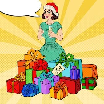 Pop art szczęśliwa kobieta w santa hat z dużymi pudełkami i kieliszkiem do szampana.