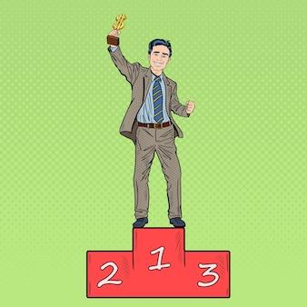Pop art szczęśliwy biznesmen trzymając złoty puchar zwycięzców. sukces biznesowy.