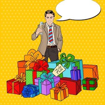 Pop art szczęśliwy człowiek z dużymi pudełkami na prezenty i kieliszkiem do szampana.