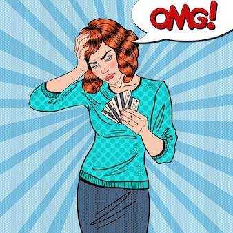 Pop art zdenerwowana kobieta z kartami kredytowymi ma ból głowy.