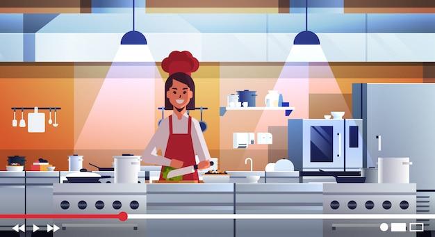 Portret blogerka jedzenie wideo kobieta kucharz w mundurze gotowanie w kuchni blogowanie wyjaśniające, jak gotować naczynie portret
