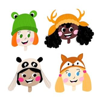 Portret dzieci różnych narodowości w śmiesznych czapkach zimowych w postaci zwierząt