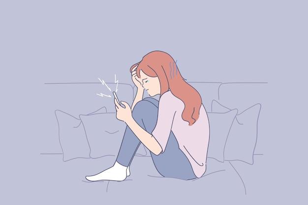 Portret młodej kobiety przygnębionej nieszczęśliwej siedzi na kanapie z telefonem i cierpi na złe myśli