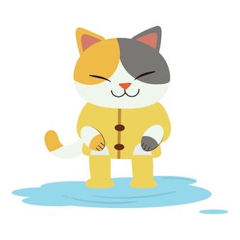 Postać uroczego kota nosi żółty płaszcz przeciwdeszczowy i buty