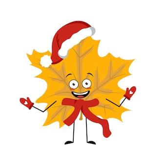 Postać z klonowego liścia z radosnymi emocjami, uśmiechniętą buzią, szczęśliwymi oczami, ramionami i nogami. wesoła jesienna roślina leśna w jesiennym żółtym kolorze w czerwonej czapce mikołaja, szaliku i rękawiczkach