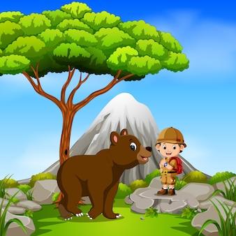Poszukiwacz przygód i niedźwiedź pozowanie z górskiej sceny