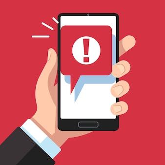 Powiadomienie mobilne o wiadomości alarmowej. ręka trzyma smartfon ze znakiem wykrzyknika