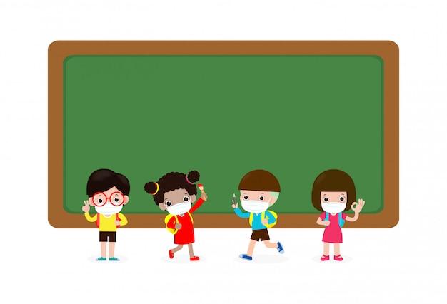 Powrót do szkoły w celu opracowania nowej koncepcji normalnego stylu życia. wielokulturowi uczniowie z maskami medycznymi stoją twarzą w pobliżu tablicy postaci z kreskówek grupa dzieci i przyjaciół ochrona przed wirusami coronavirus covid 19