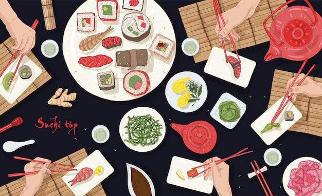 Poziomy baner z ludźmi siedzącymi przy stole pełnym japońskich posiłków w azjatyckiej restauracji i jedzących sushi