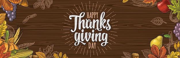 Poziomy plakat z napisem kaligrafia happy thanksgiving day. wektor kolor rocznika grawerowanie ilustracja dynia, kukurydza, liść klonu, żołądź, nasiona kasztanowca na ciemny brąz tekstury drewna.