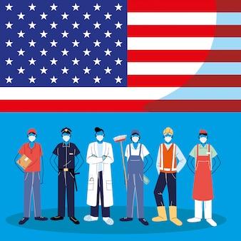 Pracownicy pierwszej linii noszący maski na twarz stojący z amerykańską flagą