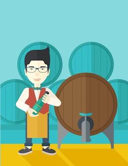 Producent wina sprawdzający wino z beczki.