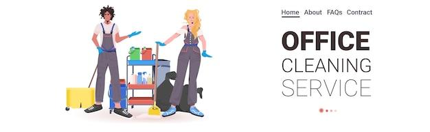 Profesjonalne środki czyszczące do biura mieszają rasę woźnych kobieta mężczyzna w mundurze ze sprzętem czyszczącym stojąc razem, kopiuj przestrzeń poziomą