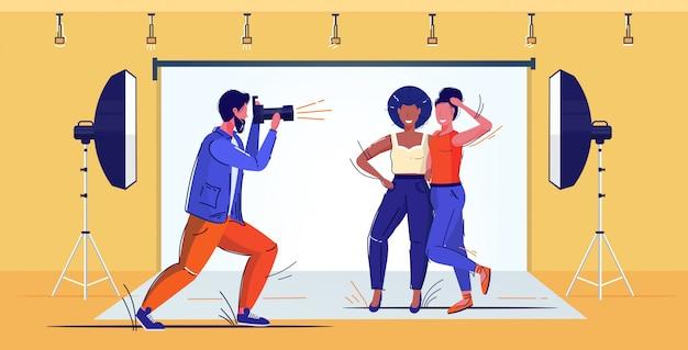 Profesjonalny fotograf za pomocą aparatu dslr mężczyzna strzelanie piękna mieszanka rasy kobiet modeli pozowanie razem nowoczesne zdjęcie studio pełnej długości szkic ilustracji wektorowych wnetrze