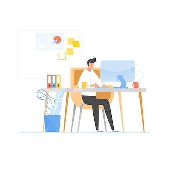 Programista lub koder siedzi przy biurku i pracuje na komputerze.