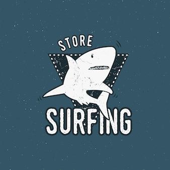 Projekt godła sklepu surfingu. rekin na trójkącie trzymanym. styl retro szorstki. szablon logo surfingu na białym tle na niebieskim tle. insygnia lato wektor.