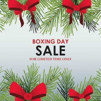 Projekt transparentu sprzedaży w drugi dzień świąt z dekoracyjnymi sosnowymi gałęziami i czerwonymi kokardkami nad szarym