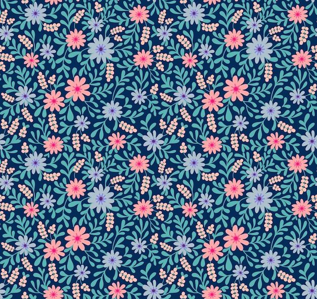 Prosty ładny wzór w małe różowo-niebieskie kwiatki na granatowym tle. styl liberty. drobny nadruk. kwiatowy bezszwowe tło. elegancki szablon do modnych nadruków.
