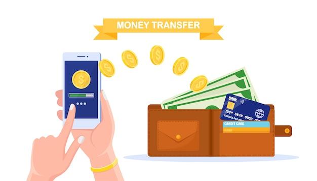 Przelew z portfela cyfrowego. cashback, koncepcja nagrody. ludzka ręka trzymająca telefon komórkowy z aplikacją bankową, torebka z gotówką, moneta, karta kredytowa, banknot. płatność online.