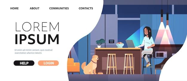 Przepracowana bizneswoman freelancer patrząca na ekran laptopa kobieta z psem pracująca w ciemnej nocnej kuchni pozioma pełna długość miejsca na kopię