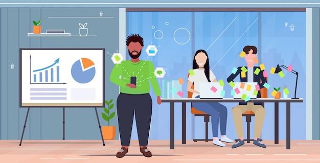 Przepracowany kierownik wyjaśnia nową strategię kolegom pokrytym karteczkami planowanie biznesowe praca zespołowa prezentacja koncepcja nowoczesne biuro wnętrze pozioma pełna długość