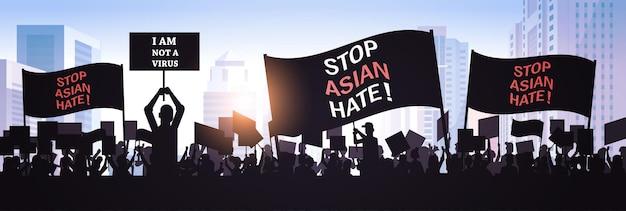 Przestań azjatycką nienawiść. sylwetki ludzi posiadających plakaty przeciwko rasizmowi. wsparcie podczas pandemii koronawirusa covid-19